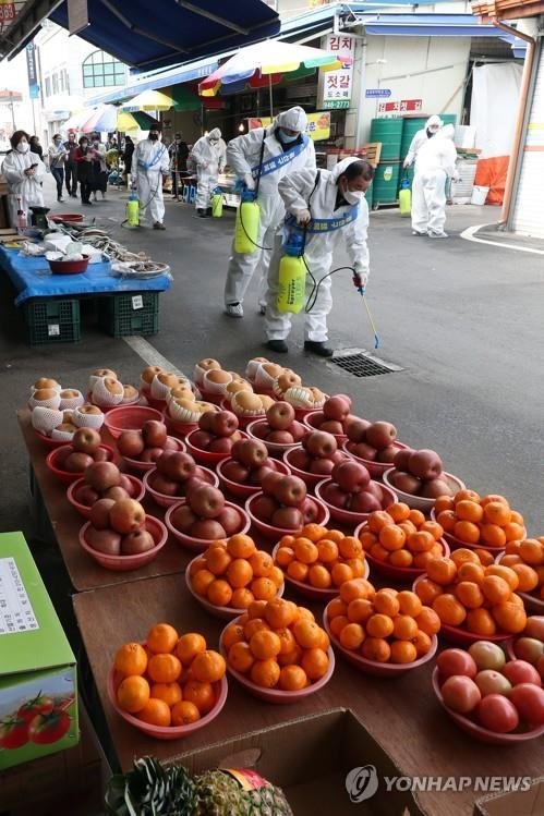 Workers disinfect a market in the southern city of Gwangju, South Korea, on Feb. 11, 2020, amid fears over the spreading new coronavirus. (Yonhap)