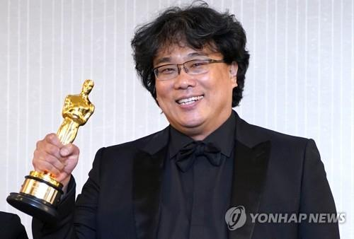 "South Korean director Bong Joon-ho holds up his Oscar trophy and smiles at a press conference held at the London West Hollywood in Los Angeles on Feb. 9, 2020 (local time), after his black comedy film ""Parasite"" took four titles at the 92nd annual Academy Awards. (Yonhap)"
