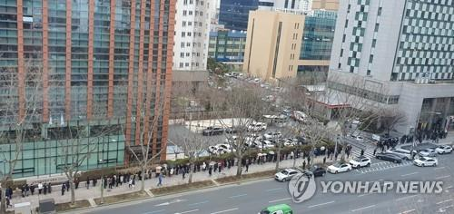 People wait in a long line for hours to buy just five masks per person at a post office in coronavirus-stricken Daegu, 300 kilometers southeast of Seoul, on Feb. 28, 2020. (Yonhap)