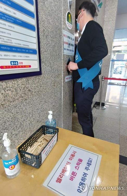 A box containing pieces of disposable wooden chopsticks for pressing elevator buttons is set next to an elevator at the city hall in Gangneung on South Korea's east coast on March 9, 2020, as part of preventive measures against the new coronavirus. (Yonhap)
