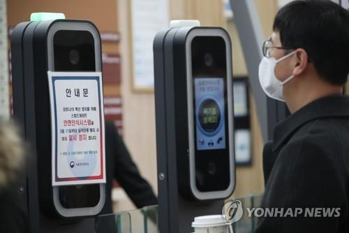 A government employee enters a gate of the government complex in Seoul on March 11, 2020, with a face mask on, as the operation of a facial recognition system to enter the complex has been suspended amid the spread of the new coronavirus. (Yonhap)