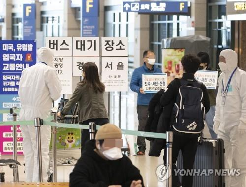 Entrants at South Korea's main gateway, Incheon International Airport, wait for a bus that will carry them to their respective houses on March 30, 2020. Starting on April 1, the country will enforce a two-week mandatory quarantine on all entrants from overseas in a drastic move to curb a steady rise in imported cases of COVID-19. (Yonhap)