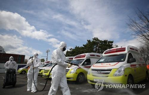 Emergency workers disinfect ambulances used for transferring the new coronavirus patients in the southeastern city of Daegu on March 29, 2020. (Yonhap)
