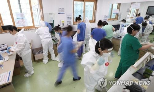 Medical workers at Dongsan Hospital in Daegu, 300 kilometers southeast of Seoul, put on protective gear as they get ready to treat novel coronavirus patients on April 9, 2020. (Yonhap)