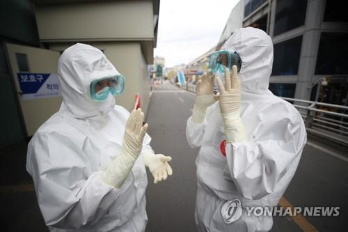 Medical workers in protective gear speak to each other before starting work at Keimyung University Dongsan Medical Center in Daegu, 300 kilometers southeast of Seoul, on April 13, 2020. (Yonhap)