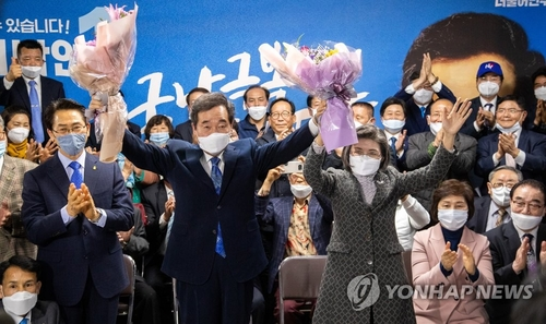 Lee Nak-yon (L), the ruling Democratic Party's parliamentary candidate for Seoul's Jongno constituency, raises up bouquets of flowers in his election office with his wife to celebrate his election win on April 15, 2020. (Yonhap)