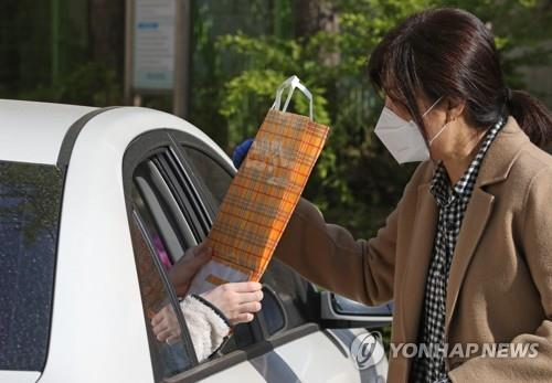 A teacher gives her student a paper bag containing national academic assessment test papers via drive-thru distribution at Yeouido Girls' High School in Seoul on April 24, 2020, amid the COVID-19 crisis. (Yonhap)