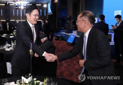 Samsung Group Vice Chairman Lee Jae-yong (L) shakes hands with Hyundai Motor Group Executive Vice Chairman Chung Eui-sun at a New Year's meeting in Seoul on Jan. 2, 2020. (Yonhap)