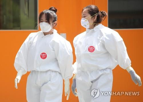 A pair of nurses not wearing protective head gear walk toward the COVID-19 patient ward to start their shifts at Keimyung University's Dongsan Hospital in Daegu, 300 kilometers southeast of Seoul, on May 12, 2020. (Yonhap)