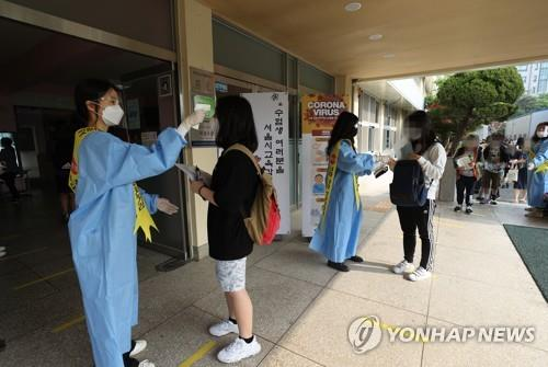 Applicants for this year's school qualification examination have their temperatures checked at a middle school in Seoul on May 23, 2020. The exam for a general equivalency diploma was supposed to be held in April but was delayed twice due to the coronavirus. (Yonhap)
