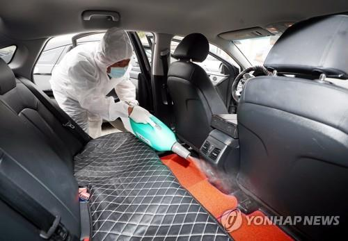 A taxi company official disinfects a vehicle in the western city of Incheon on May 22, 2020. The number of taxi users has reportedly decreased over the past several days after a taxi driver in the city recently tested positive for the coronavirus. (Yonhap)