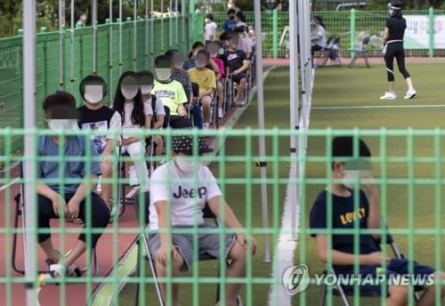 Elementary school students wait in line to take COVID-19 tests at a clinic temporarily set up at a school in Seoul's southwestern ward of Gwanak on June 28, 2020, after new infections related to a church located nearby were reported. (Yonhap)