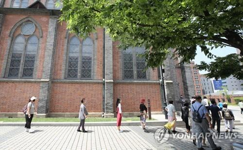 People keep distance from one another while waiting in line for Mass at Myeongdong Cathedral in central Seoul on June 28, 2020. (Yonhap)