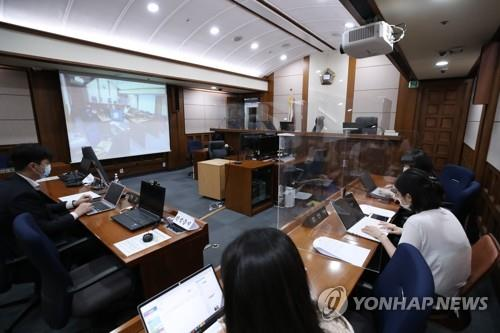 Reporters wait for the hearing to begin on the extradition case of Son Jung-woo, who ran one of the world's biggest child porn sites, at the Seoul High Court on July 6, 2020. (Yonhap)