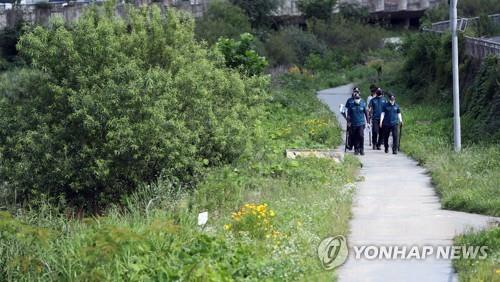 Police officers search a trail along a stream for a man in his 60s in the southwestern city of Gwangju on July 7, 2020, after he was confirmed to have been infected with the new coronavirus and went into hiding with his smartphone turned off. (Yonhap)