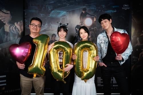 "Director Yeon Sang-ho (L) and cast members of the zombie action film ""Peninsula"" celebrate the film's surpassing of 1 million in total admissions on July 18, 2020, in this photo provided by NEW. (PHOTO NOT FOR SALE) (Yonhap)"