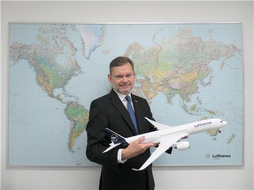 In this photo, taken on July 30, 2020, Alejandro Arias, general manager of Lufthansa's South Korean operations, stands holding a model airplane of the A350-900 against a map of the world at the airline's Seoul office. (Yonhap)