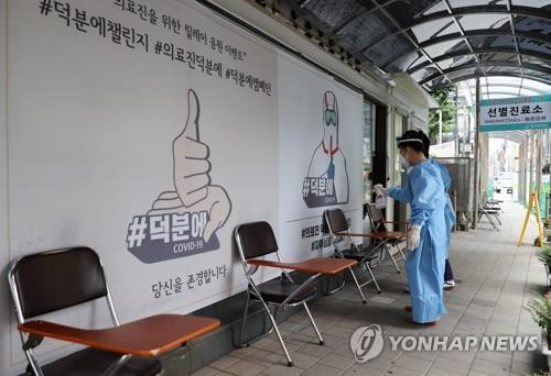 This undated file photo shows two people, wearing protective masks and a full gown, spraying disinfectants around chairs at a selected clinic for COVID-19. (Yonhap)