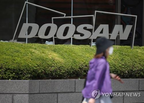 This undated file photo shows a passerby walking past a logo of Doosan Group in front of the group's building in Seoul. (Yonhap)