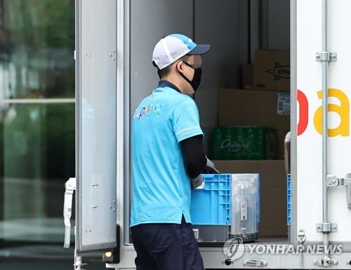 A delivery man moves parcels in Seoul on Aug. 14, 2020. (Yonhap)