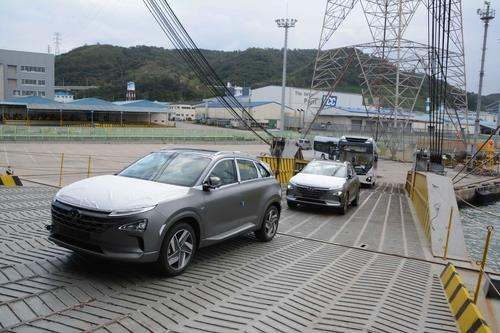 This photo, taken Sept. 28, 2020, and provided by Hyundai Motor, shows two Nexo hydrogen fuel cell electric vehicles and two hydrogen Elec City buses being loaded onto a ship for export to Saudi Aramco at the carmaker's port in Ulsan, 414 kilometers southeast of Seoul. (PHOTO NOT FOR SALE) (Yonhap)