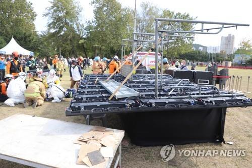 This photo provided by Incheon's Bupyeong Fire Station shows firefighters taking care of injured citizens at the former site of USFK base Camp Market on Oct. 14, 2020, after they were hurt by the collapse of an LED billboard installed for the former base's public opening ceremony. (PHOTO NOT FOR SALE) (Yonhap)