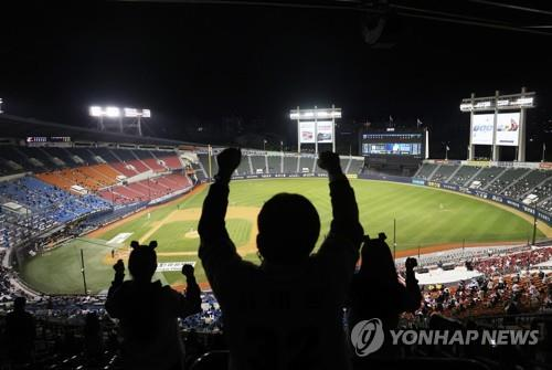 Fans sit apart and cheer while watching a Korea Baseball Organization regular season game between the Hanwha Eagles and the Doosan Bears at Jamsil Stadium in Seoul, on Oct. 13, 2020. The government eased social distancing rules over the coronavirus, allowing sports leagues to admit crowds of up to 30 percent of stadium capacities. (Yonhap)
