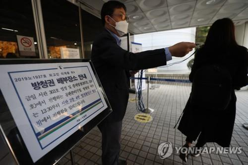 Spectators receive a ticket for the retrial of Lee Jae-yong, vice chairman of Samsung Electronics Co, in front of the Seoul High Court on Oct. 26, 2020. (Yonhap)