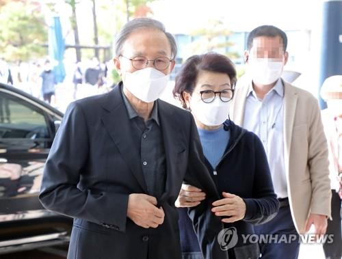 Former President Lee Myung-bak, helped by his wife, Kim Yoon-ok, arrives at Seoul National University Hospital in Seoul on Oct. 30, 2020, to see a doctor.(Yonhap)