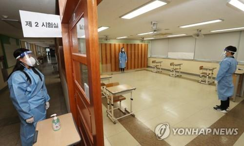 Proctors demonstrate their quarantine gear at a test room only for test takers with COVID-19 symptoms at a high school in Sejong, central South Korea, on Dec. 2, 2020, one day ahead of the country's nationwide college entrance test. (Yonhap)