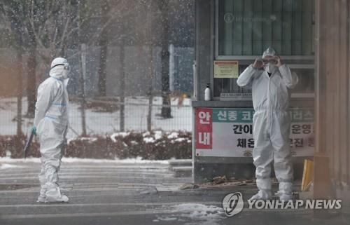 Two medical staff members stand outside the coronavirus testing center at Dongbu Detention Center in southeastern Seoul on Jan. 12, 2021. (Yonhap)