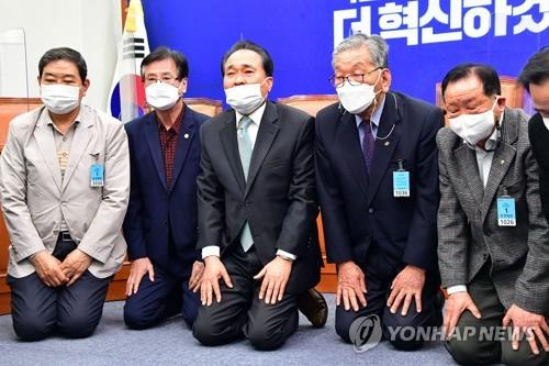 Members of the Democratic Party's senior committee kneel at a press conference over the results of the April 7 by-elections at the National Assembly in Seoul on April 12, 2021. (Yonhap)