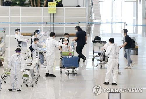 Quarantine officials attend to passengers who arrived from overseas at Incheon International Airport, west of Seoul, on May 5, 2021. South Korea has seen a steady increase in coronavirus infections in recent weeks, with the daily count reaching 676 on May 5. (Yonhap)