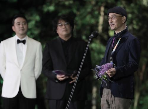 """Director Lee Joon-ik (R) of """"Book of Fish"""" delivers an acceptance speech after winning the grand prize at the 57th Baeksang Arts Awards (BAA) on May 13, 2021, in this photo provided by the BAA secretariat. (PHOTO NOT FOR SALE) (Yonhap)"""