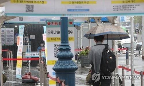 A person waits to take a virus test while holding an umbrella at a screening center in Seoul Station, downtown Seoul, on Sept. 29, 2021. (Yonhap)