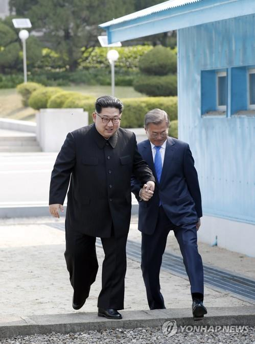 문재인 대통령과 북한 김정은 국무위원장이 4월 27일 판문점 군사정전위원회 회담장 사이 군사분계선을 함께 손을 맞잡고 북에서 남으로 넘고 있다.