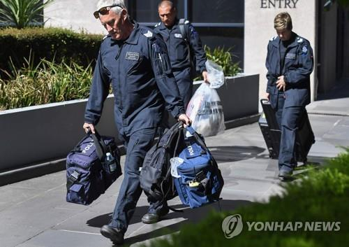 호주 멜버른 이탈리아 영사관에 배달된 가방을 갖고 나오고 있는 경찰