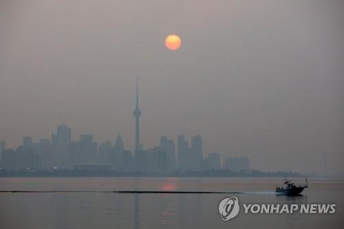 20일(현지시간) 아침 캐나다 토론토에 연기가 자욱한 가운데 해가 뜨고 있다. [로이터=연합뉴스]
