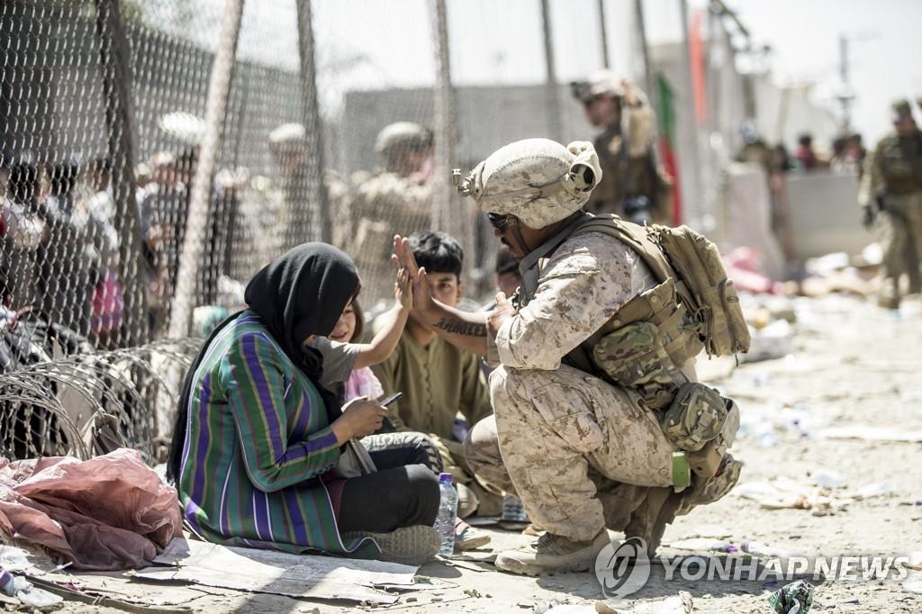 아프간 카불공항에서 미 해병대원이 아프간 어린이와 손인사를 하고 있다. [미 해병대 사령부 제공/AP=연합뉴스 자료사진]