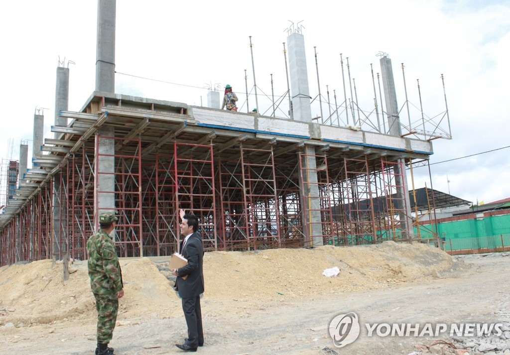 This file photo shows an official from the Korea International Cooperation Agency (R) and a Colombian military official touring a construction site in Bogota on July 19, 2013, where the Korea-Colombia Rehabilitation Center is being constructed. (Yonhap)