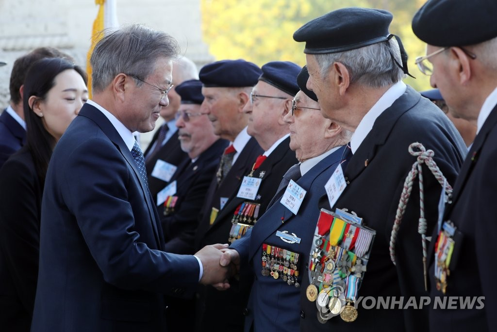 South Korean President Moon Jae-in (L) shakes hands with a French Korean War veteran during an official welcome ceremony held in Paris on Oct. 15, 2018, to mark his four-day state visit to France. (Yonhap)