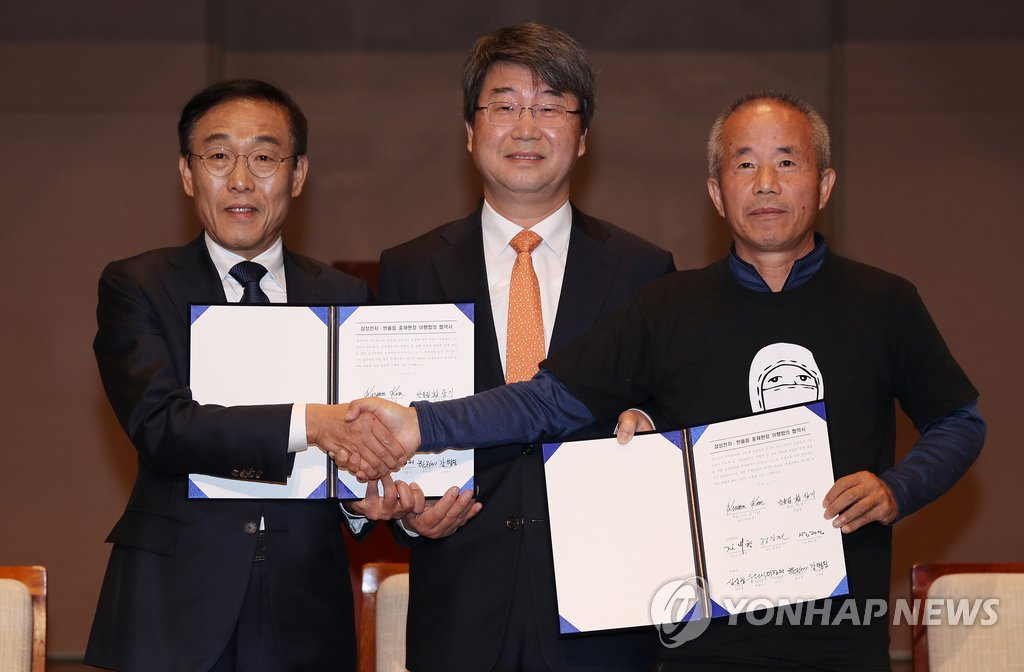 Samsung Electronics President and CEO Kim Ki-nam (L), Lawyer Kim Ji-hyung of the mediation committee (C), and Hwang Sang-ki, the head of the Supporters for the Health and Rights of People in the Semiconductor Industry, pose for a photo after signing the agreement on compensating work-related diseases in Seoul on Nov. 23, 2018. (Yonhap)