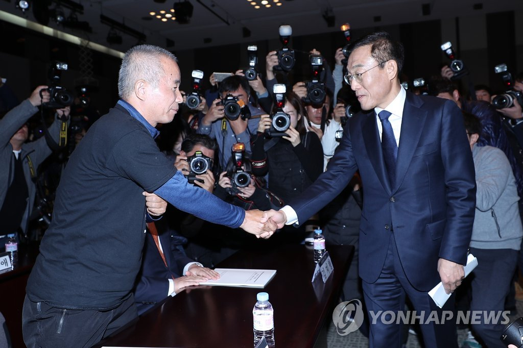 Samsung Electronics President and CEO Kim Ki-nam (R), and Hwang Sang-ki, the head of the Supporters for the Health and Rights of People in the Semiconductor Industry shake hands after signing the agreement on compensating work-related diseases in Seoul on Nov. 23, 2018. (Yonhap)