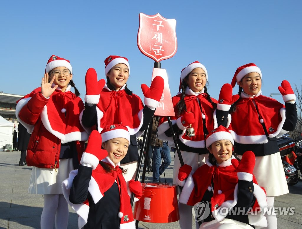 Children pose for a photo with the Salvation Army's donation kettle in central Seoul in this file photo taken Nov. 30, 2018. (Yonhap)