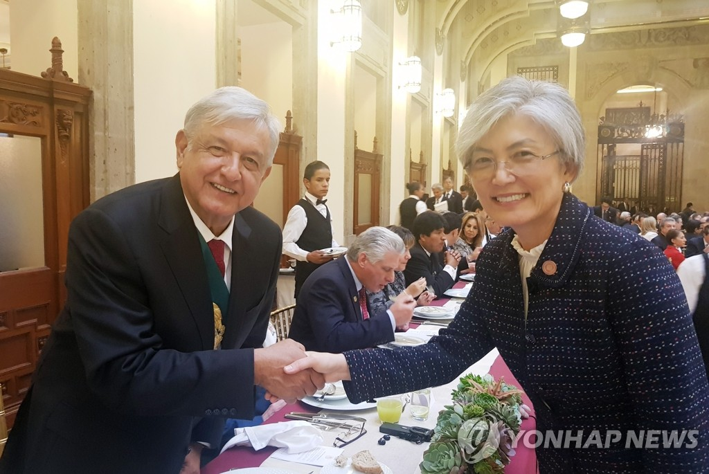 In this photo, provided by Seoul's foreign ministry, South Korean Foreign Minister Kang Kyung-wha (R) poses for a photo with Mexico's new president, Andres Manuel Lopez Obrador, in the Latin American country on Dec. 1, 2018. (Yonhap)