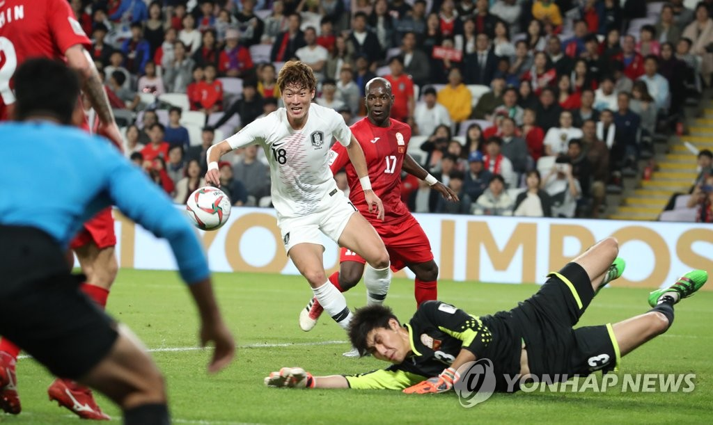 Hwang Ui-jo of South Korea (C) goes after the ball with Kutman Kadyrbekov of Kyrgyzstan down on the field during the teams' Group C match at the Asian Football Confederation Asian Cup at Hazza Bin Zayed Stadium in Al Ain, the United Arab Emirates, on Jan. 11, 2019. (Yonhap)