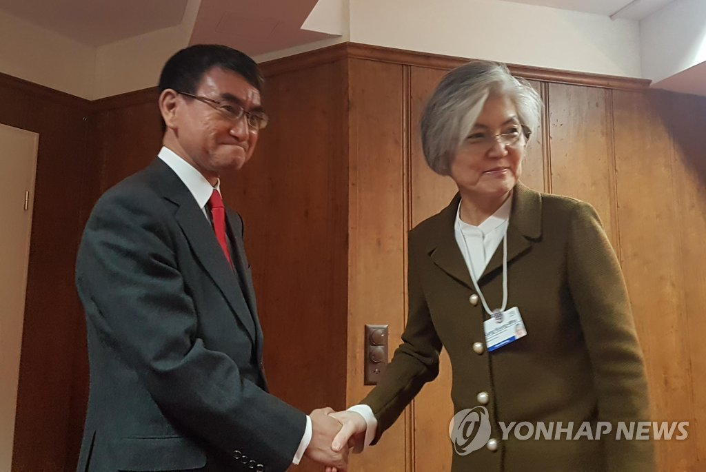 This file photo, taken on Jan. 23, 2019, shows Foreign Minister Kang Kyung-wha (R) shaking hands with her Japanese counterpart, Taro Kono, before their talks on the sidelines of the World Economic Forum in Davos, Switzerland. (Yonhap)
