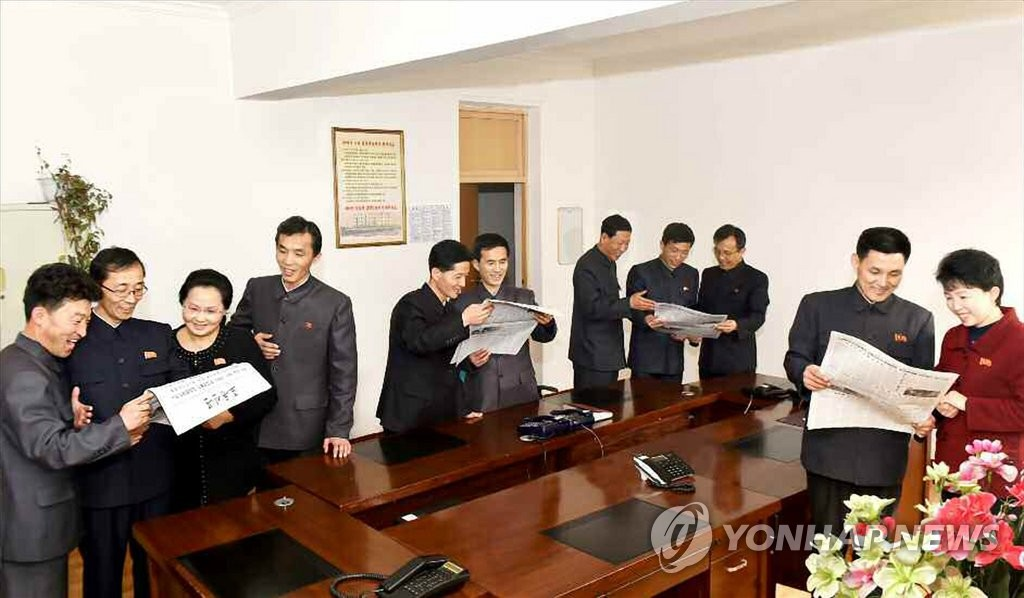 In this file photo, published by North Korea's main newspaper, the Rodong Sinmun, on March 6, 2019, North Korean workers read the daily's report on their country's leader Kim Jong-un's return from his Vietnam trip. Kim returned a day earlier by train from Hanoi where he met U.S. President Donald Trump for a second summit. The meeting ended abruptly without an agreement. (For Use Only in the Republic of Korea. No Redistribution) (Yonhap)