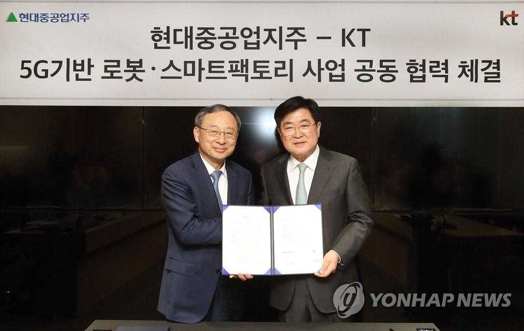 KT Chairman Hwang Chang-gyu (L) and Kwon Oh-gap, vice chairman of Hyundai Heavy Industries, pose after signing a memorandum of understanding on a 5G-based smart factory during a ceremony held at the KT building in Seoul on May 12, 2019, in this photo provided by the telecom operator. (PHOTO NOT FOR SALE) (Yonhap)