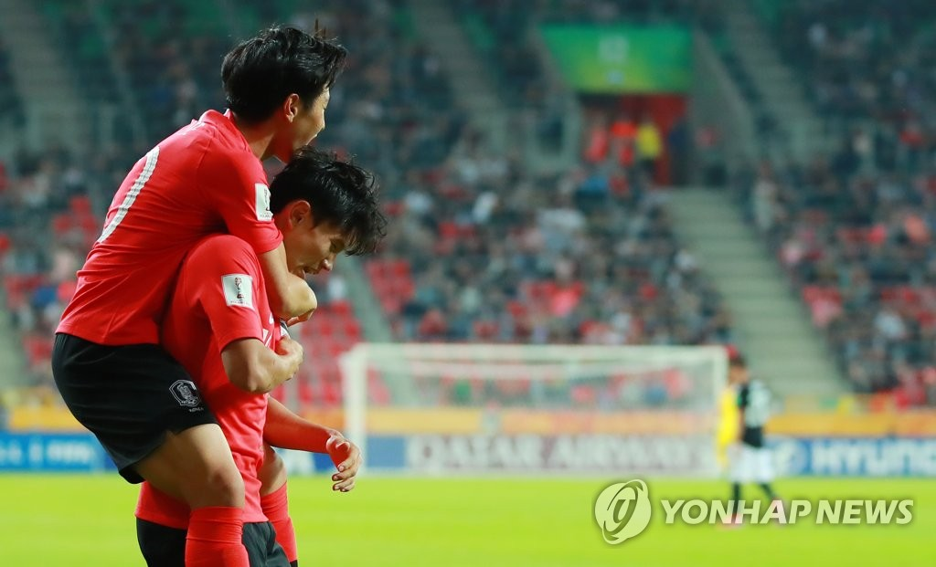 Lee Kang-in of South Korea (L) jumps on the back of teammate Cho Young-wook after Cho scored a goal against Argentina in the teams' Group F match at the FIFA U-20 World Cup at Tychy Stadium in Tychy, Poland, on May 31, 2019. (Yonhap)